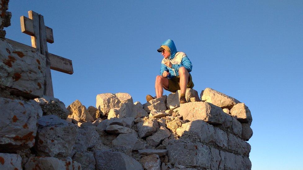 Goran Lončarević sedi na ruševinama kapele na vrhu Rtnja