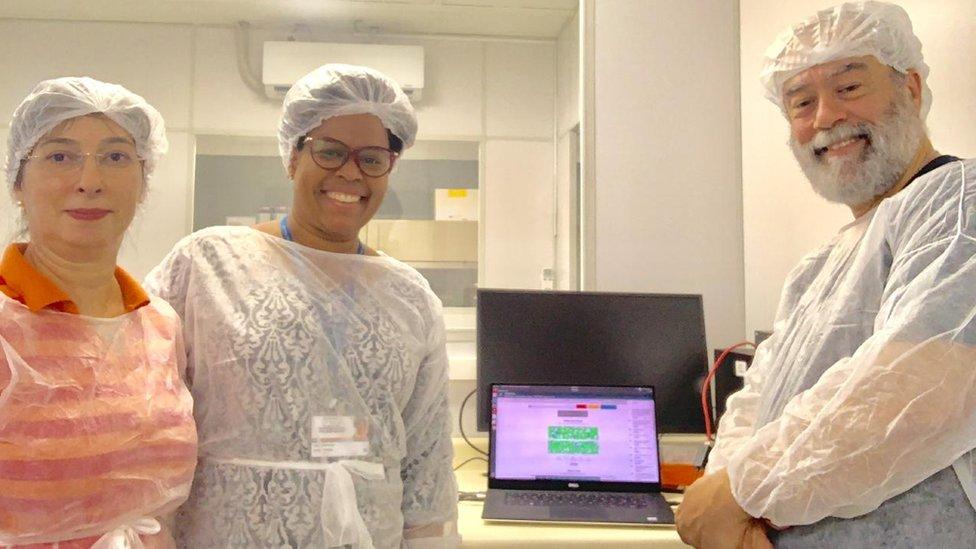 Com jalecos e toucas, Claudia Gonçalves, Jaqueline Goes e Claudio Sacchi sorriem para foto de dentro de laboratório