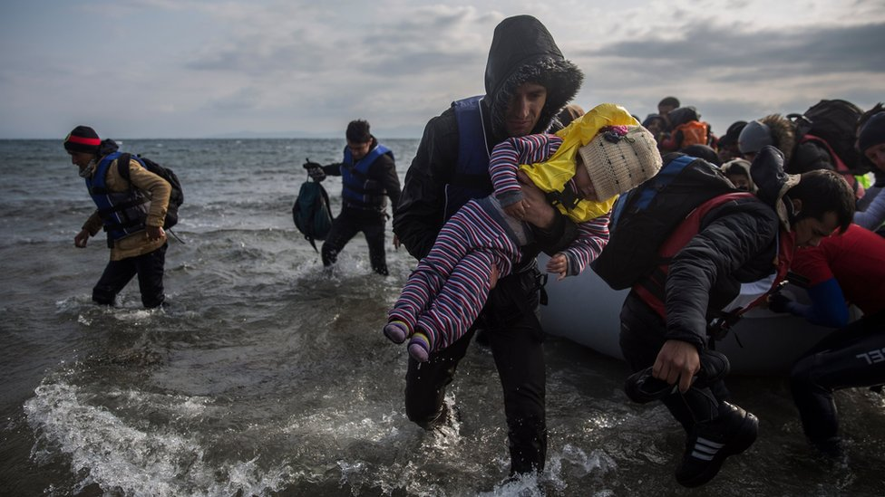 Refugees and migrants disembark a dinghy after arriving on the island of Lesbos from Turkey