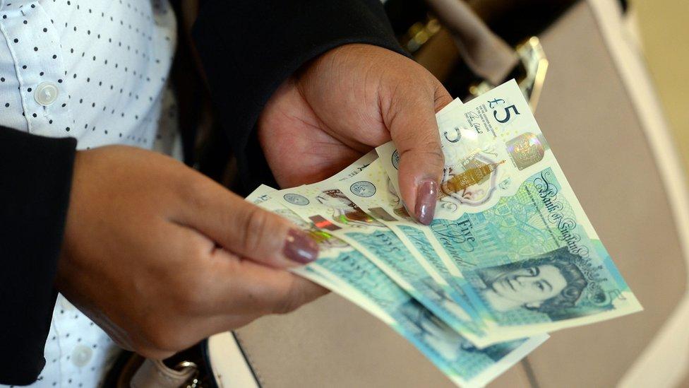 Lady holding pound notes