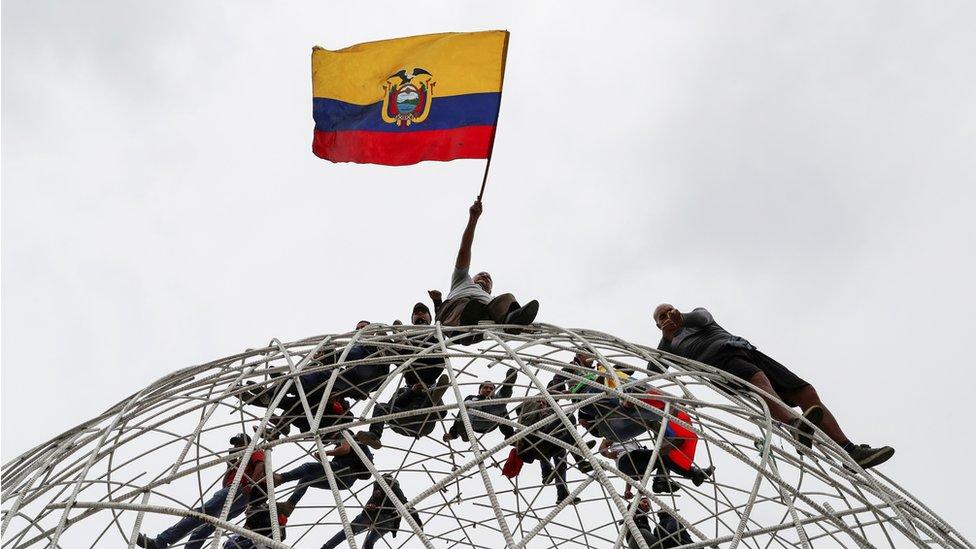 Manifestantes trepados en una escultura, con la bandera de Ecuador.