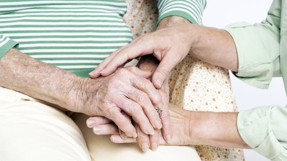 Elderly woman being comforted by a carer