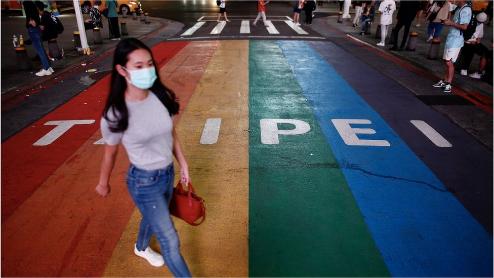 A pedestrian wearing a mask crosses the street in Taipei, Taiwan, 11 May 2021. Taiwan Health and Welfare Minister Chen Shih-chung announced during a press conference on 11 May, that Taiwan has entered the community transmission stage of COVID-19 following the emergence of six domestic cases of the disease that have unknown sources of infectio