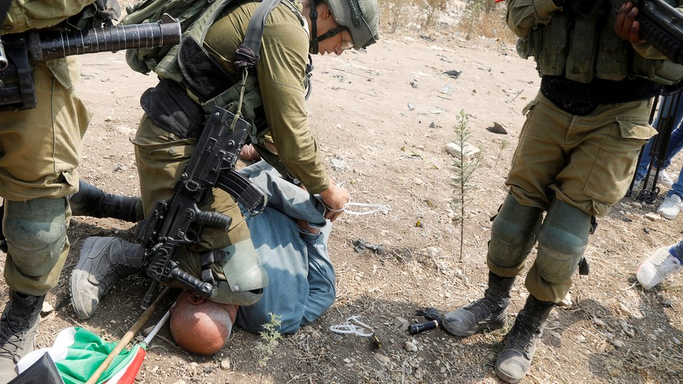 Israeli soldier condemned for putting knee on Palestinian protester's neck thumbnail