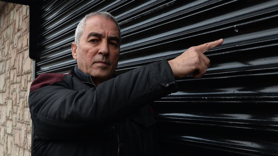 Pat Sheehan pointing at damage caused by a shot fired at a Sinn Fein office