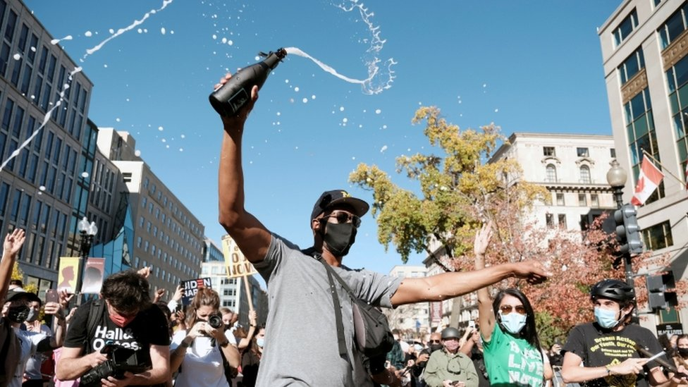 A man sprays champagne as people celebrate after news media declared Biden the winner of the election in Washington