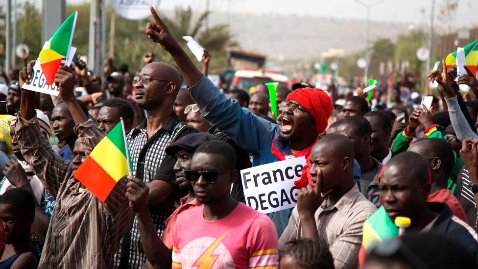 "A man in a crowd shouts as he holds a sign that reads, ""France get out"" during a protest against French and UN forces based in Mali - Bamako, 10 January 2020"