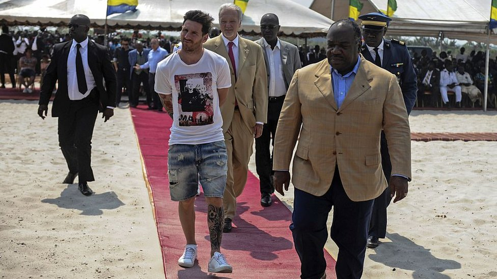 Argentinian soccer player and four-time FIFA Ballon d'Or winner Lionel Messi (C) is given a tour during the start of construction of the Port-Gentil Stadium by the President of Gabon, Ali Bongo Ondimba (R) in the Ntchengue district of Port-Gentil on July 18, 2015.