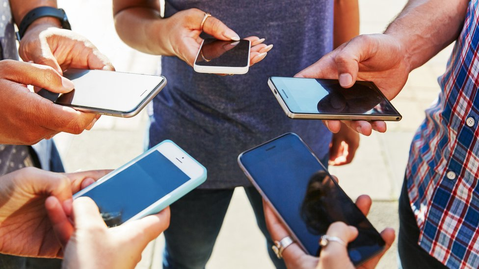 Five people stand in a circle holding their smartphones in front of them