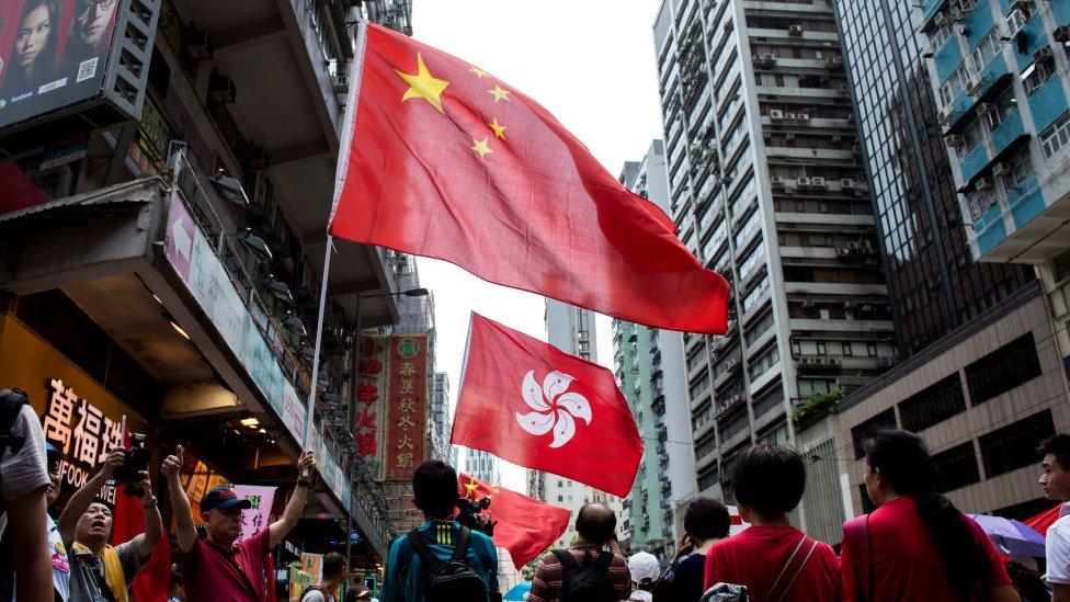 Manifestantes proChina ondean las banderas de China y de Hong Kong durante un mitin progubernamental en esa isla.