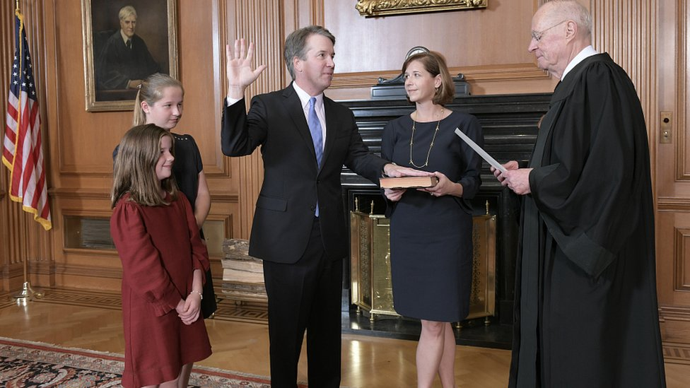 Brett Kavanaugh, watched by his family, is administered the judicial oath by Justice Anthony Kennedy