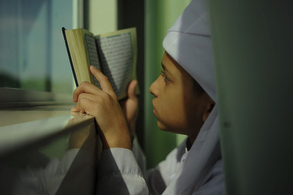 A Malaysian Muslim boy reads a copy of the Koran at his school's mosque during the holy fasting month of Ramadan in Bentong, outside Kuala Lumpur on 15 June 2016.