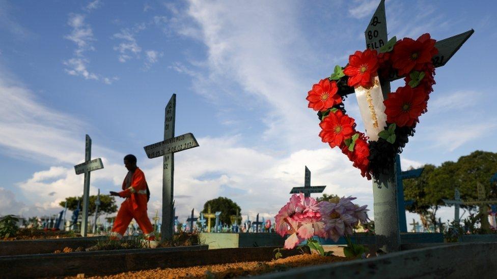 Cemitério com coroas de flores em locais onde pessoas estão enterradas