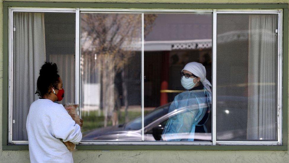 Una joven mira a una mujer a través de una ventana