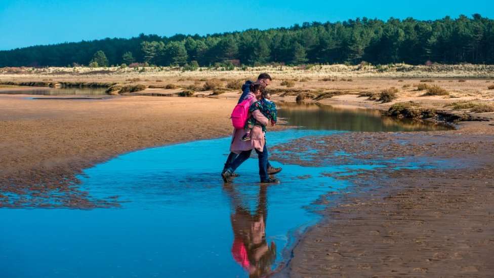 People walk on Norfolk beach