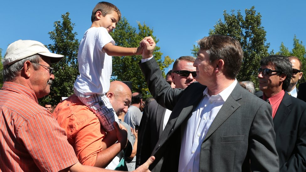 Bosnian President Zeljko Komsic shakes hands with Kenan Jakupovic (riding on the shoulders of his father Sead Jakupovic) following the groundbreaking of a sebilj, a wooden and stone fountain, at the intersection of Morganford and Gravois on Sunday, Sept. 29, 2013