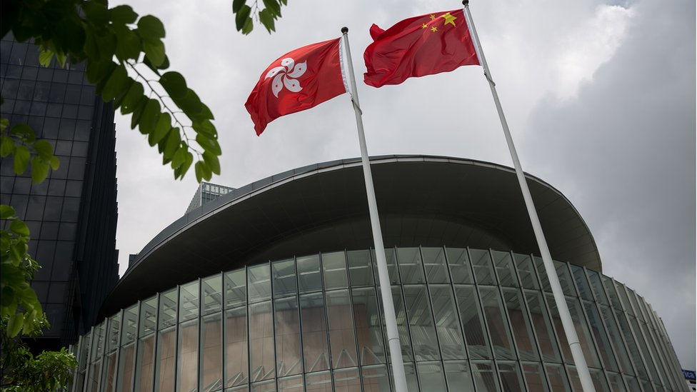 A Chinese national flag (R) and a Hong Kong national flag (L) fly outside the Legislative Council complex in Hong Kong, China, 15 July 2016