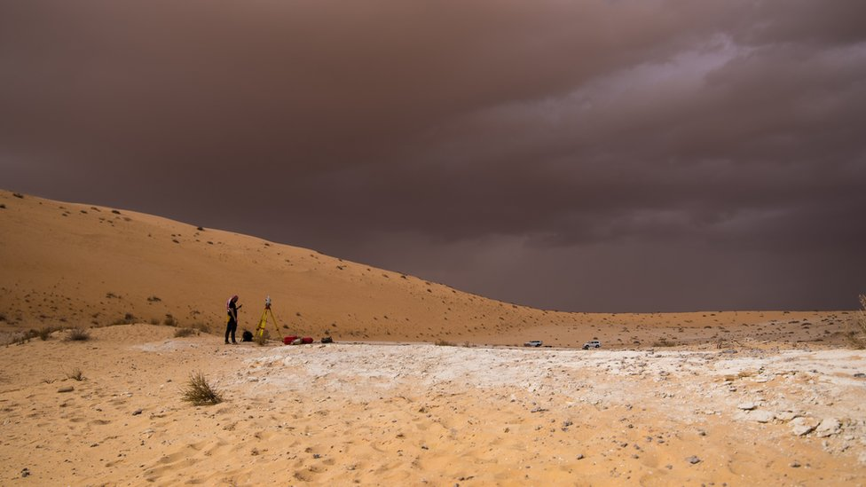 A bright desert against a dark, stormy looking sky. A scientist stands in middle distance.