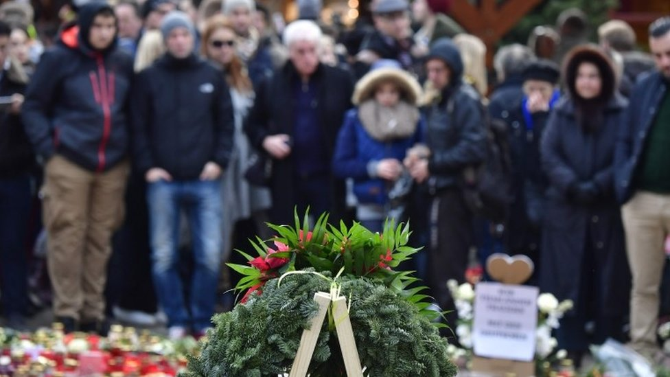 People mourn at a makeshift memorial for the victims of the Christmas market attack near the Kaiser-Wilhelm-Gedaechtniskirche (Kaiser Wilhelm Memorial Church) in Berlin on December 24, 2016