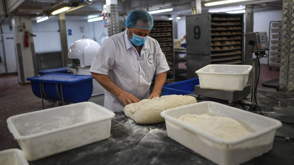 A baker is seen wearing a face mask while working at The Bread Factory on April 14, 2020 in London, England