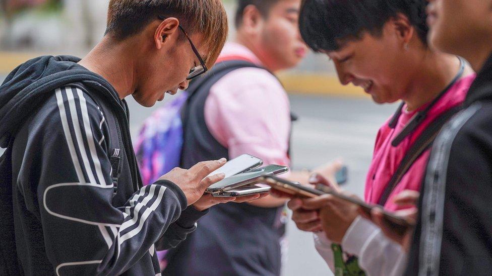 Jóvenes viendo el celular en Shanghai.
