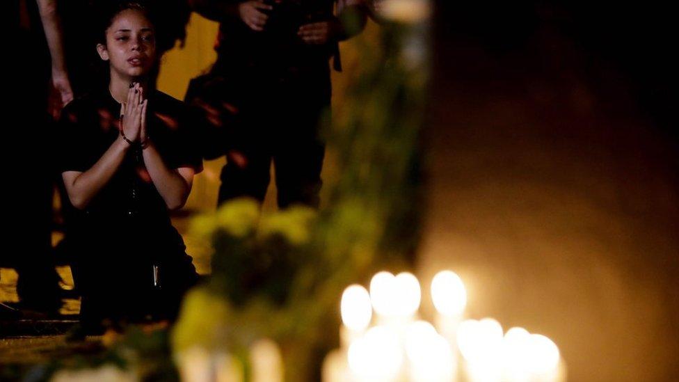 Niña reza por víctimas del tiroteo en la escuela de Brasil.