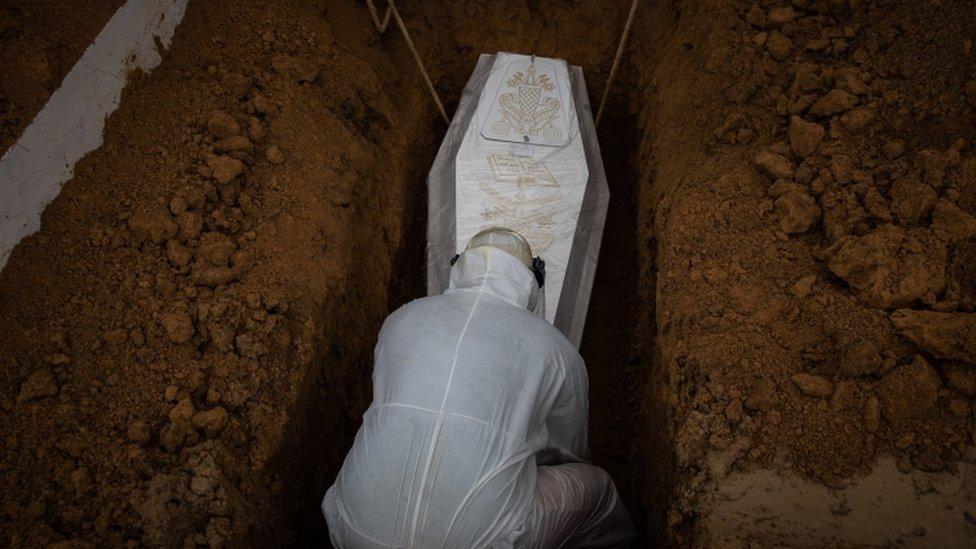 Caixão de vítima da covid-19 sendo enterrado em Manaus