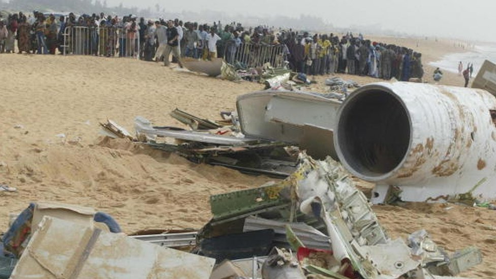 People stand behind barriers as they look at the debris of an air plane crash in Benin ( 26 December 2003)
