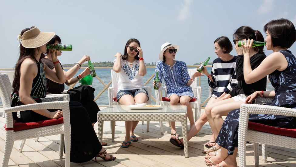 A group of Chinese female tourists gather at a jetty bar in Maldives