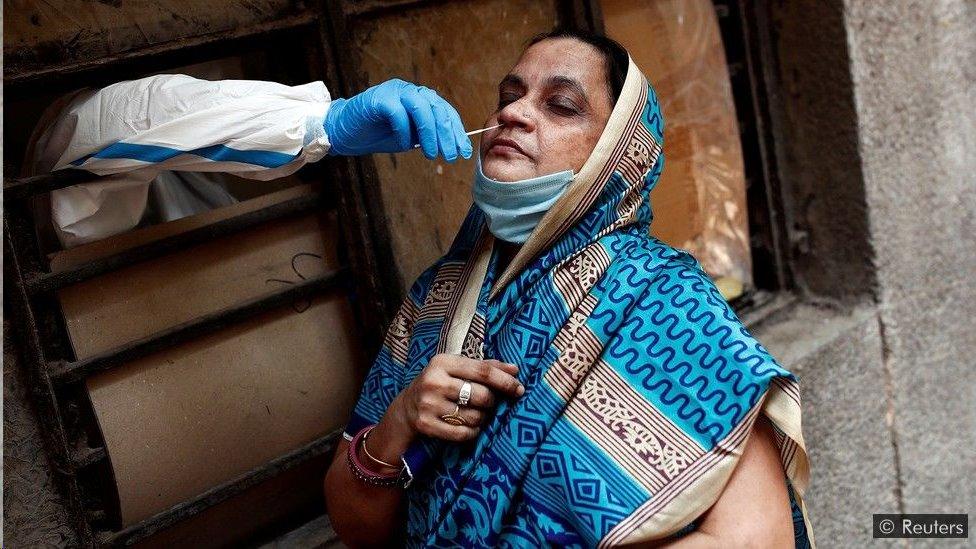 Um trabalhador médico coleta uma amostra para testar o Covid-19 em Nova Déli, na Índia