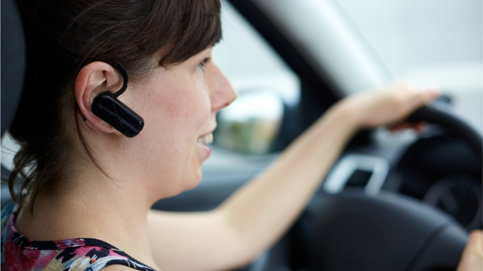 Woman talking in a car with phone headset
