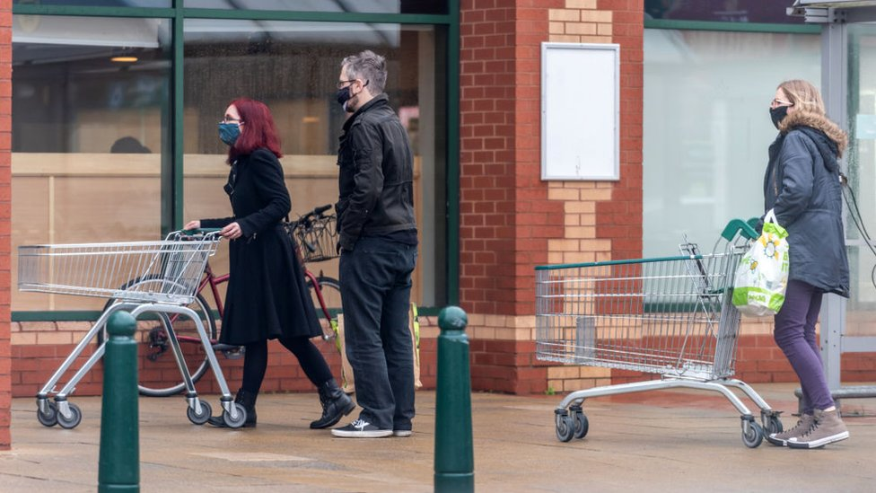 Shoppers queueing outside a Morrisons store