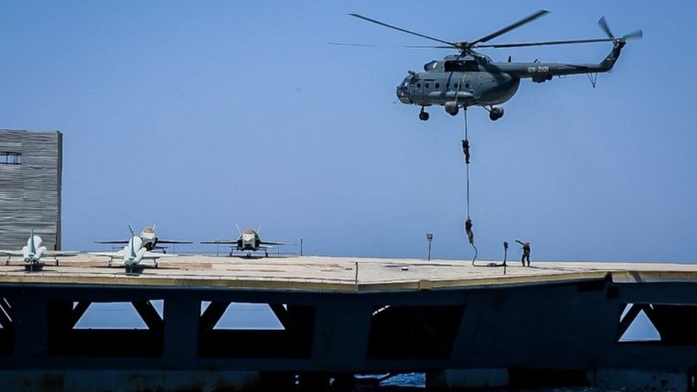 Iranian soldiers jump on the mock carrier