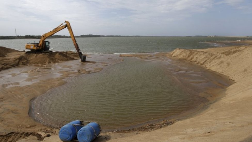 A machine works on the mouth of Rio Doce to enlarge its connection with the sea in Regencia village