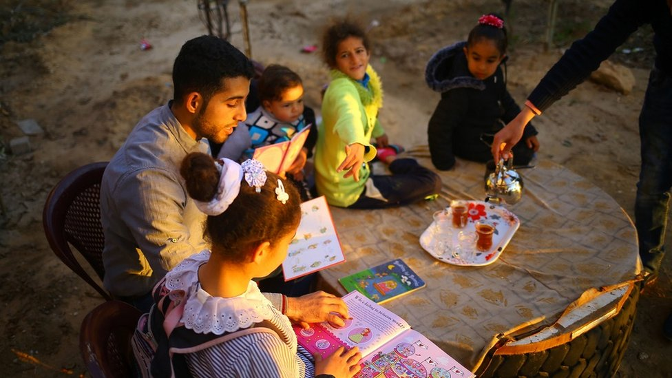 A man reads to a group of children in a Palestinian garden