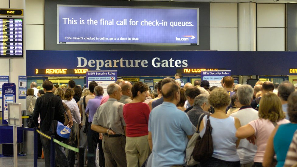 Passengers standing by an airport departure gate sign