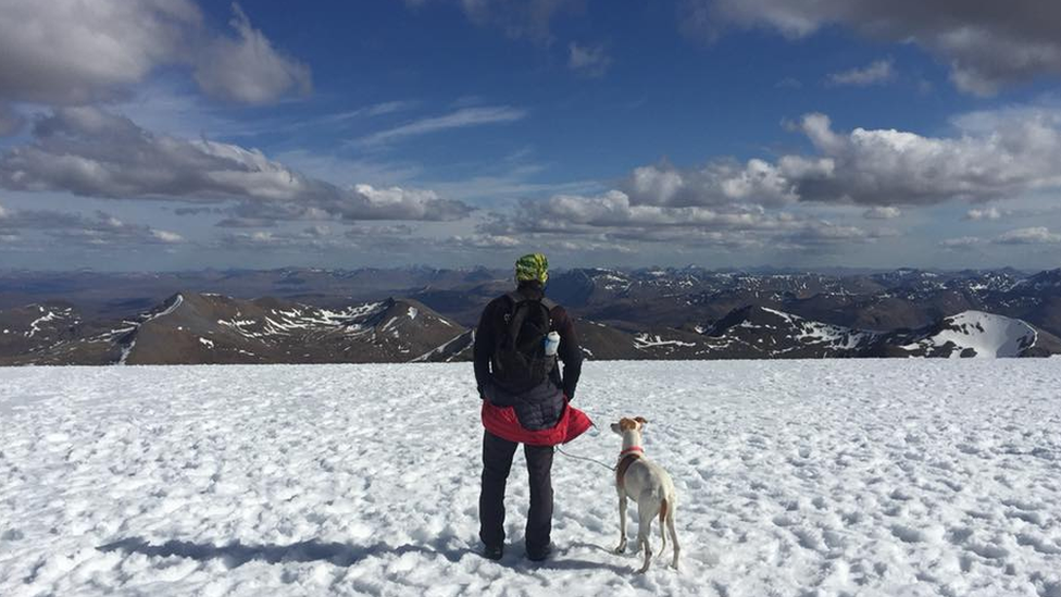 Chris Lewis and Jet in the snow overlooking the mountains