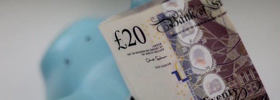 Twenty pound notes in a piggy bank
