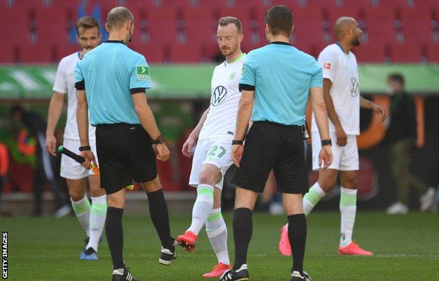 Jugadores chocan los botines con los árbitros