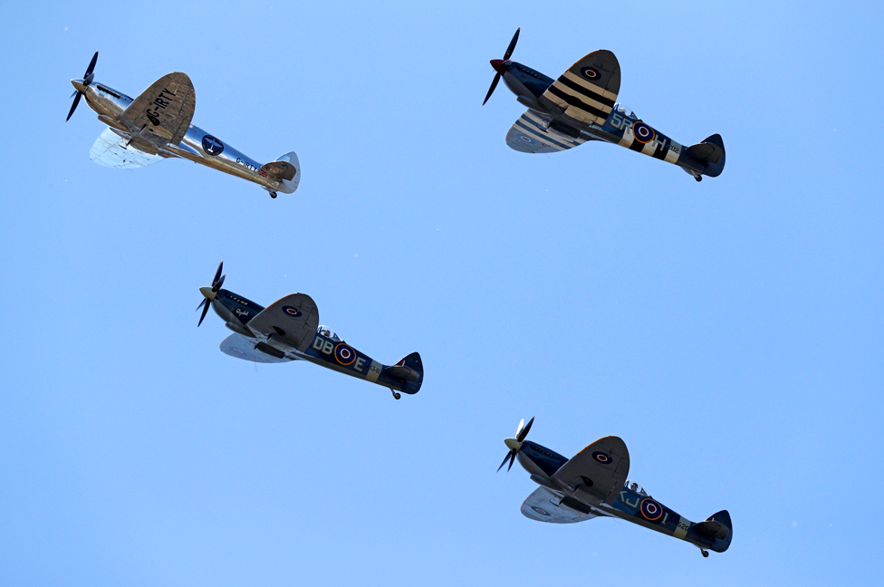 A restored silver World War Two Spitfire plane is escorted by three others