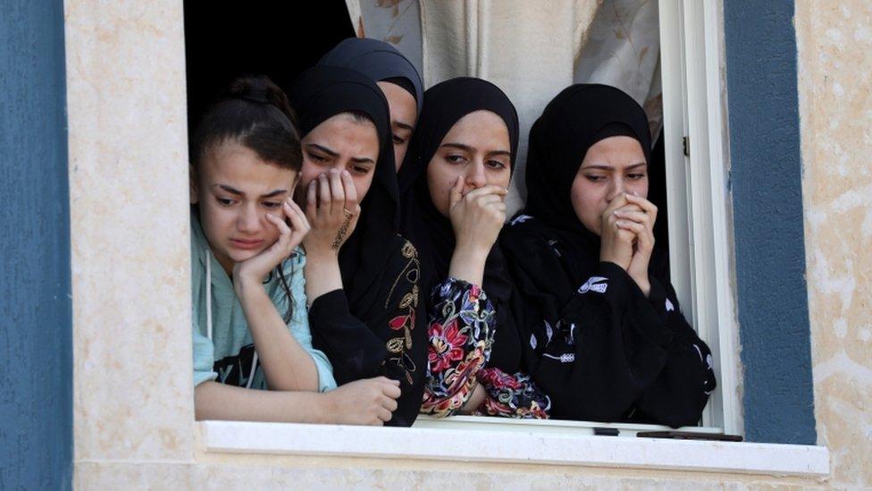 Familiares palestinos observan cómo los dolientes llevan el cuerpo de Yaseen Hamad durante su funeral en Cisjordania el 16 de mayo.