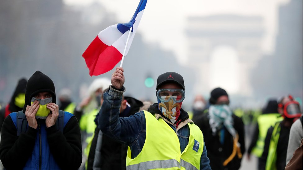 "Masked protesters wearing yellow vests, a symbol of a French drivers"" protest against higher fuel prices, take part in a demonstration on the Champs-Elysees in Paris, France, November 24, 2018."