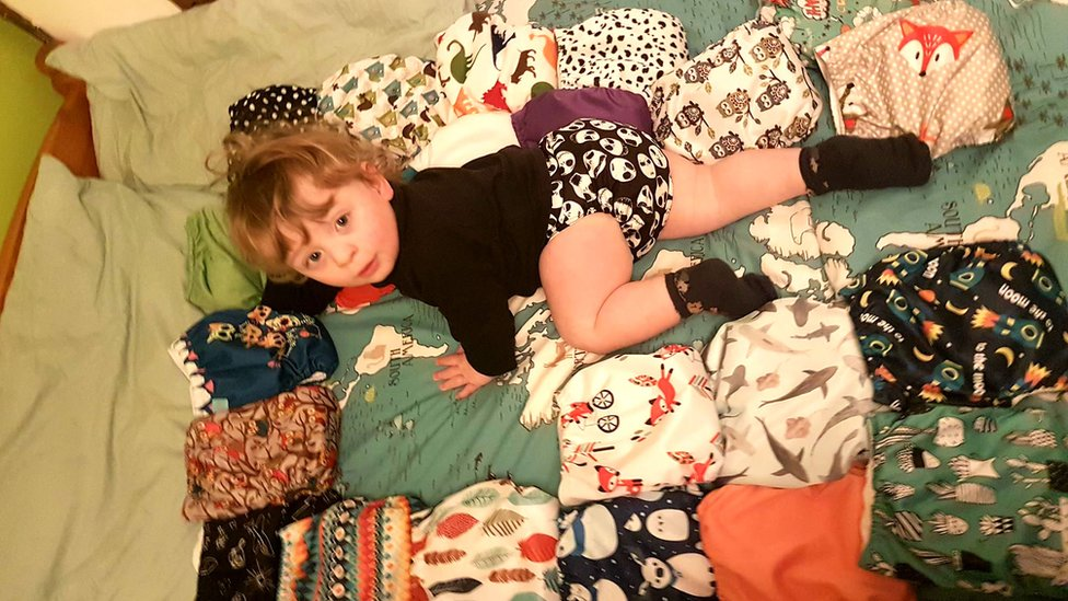 Toddler on a bed surrounded by nappies
