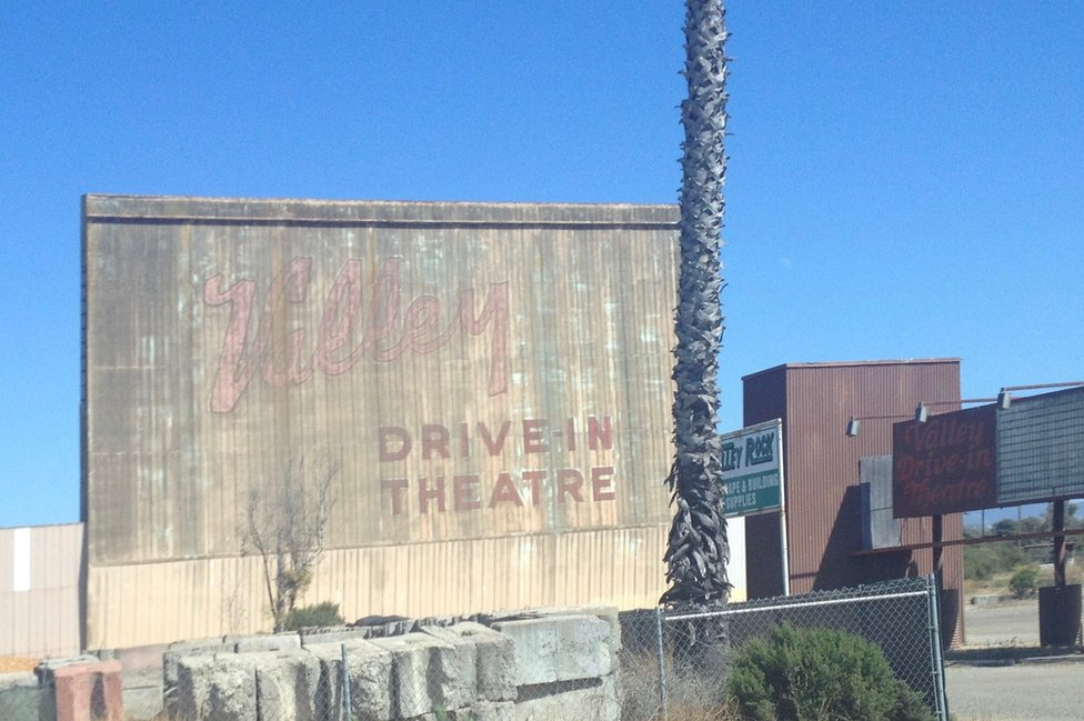 """Remnants of an old movie theatre lie on a concrete wall which reads """"Valley drive in theatre""""."""""""