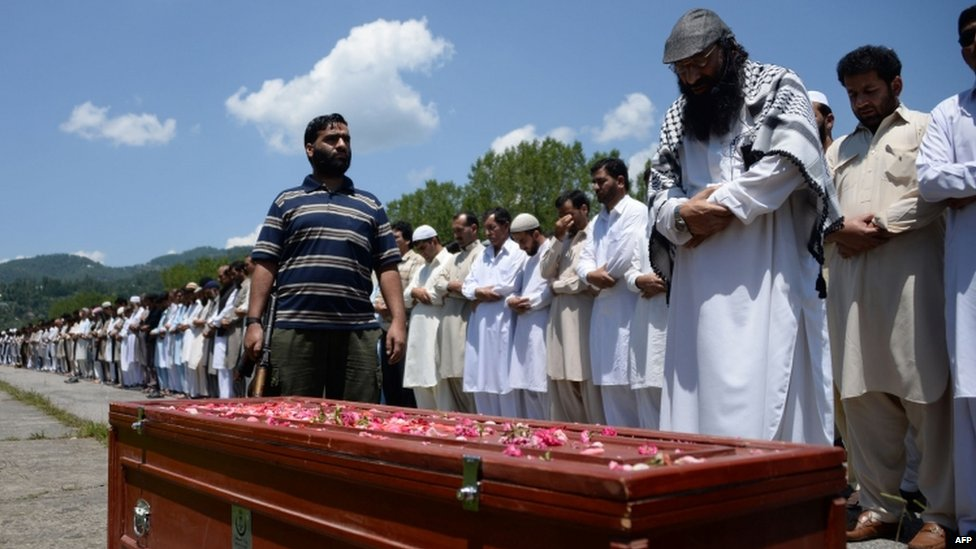 The head of the Kashmiri militant group Hizbul Mujahideen Syed Salahuddin (right) leads prayers for an alleged Pakistani militant killed in Indian-administered Kashmir during his funeral in Rawlakot in Pakistan-administered Kashmir