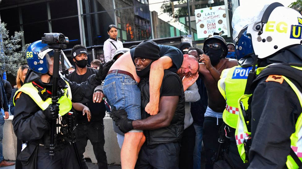 A protester carried an injured counter-protester to safety, near Waterloo station