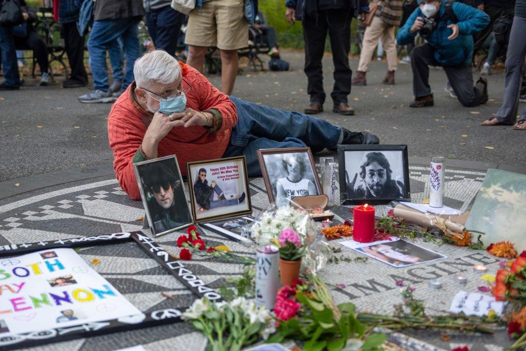 Un hombre se toma un foto frente a unas fotos y recuerdos conmemorativos de la vida de John Lennon en Strawberry Fields, Central Park, Nueva York