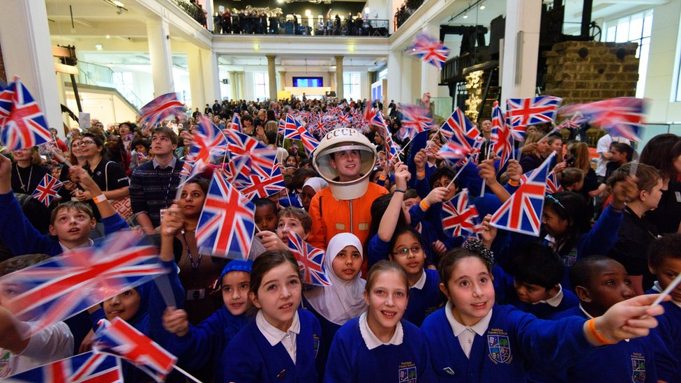 Children waving union flags, and a man standing in a mock Russian space suit at the Science Museum in London