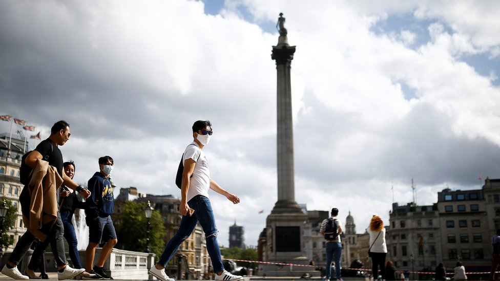 People wearing protective face masks walks through Trafalgar Square, amid the coronavirus (COVID-19) outbreak, in London