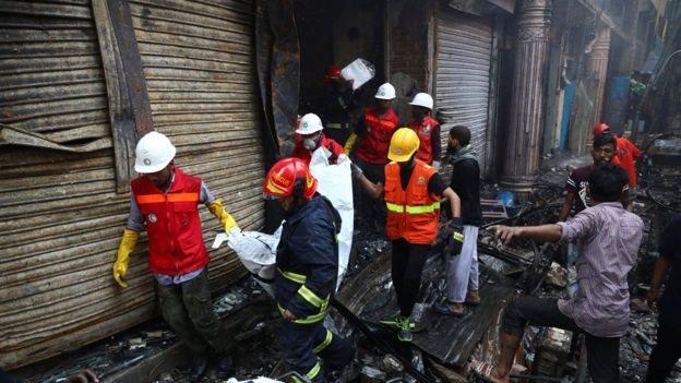 Sukarelawan menyelamatkan sebuah tubuh dari gudang terbakar.